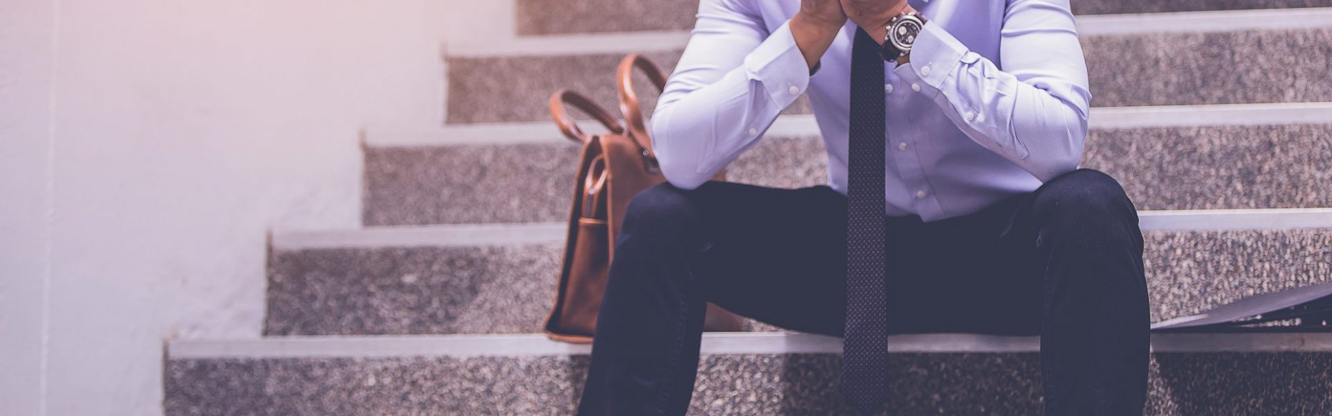 stressed-businessman-with-headache-sitting-at-stairway-disappointed-for-job-search-1980x1320